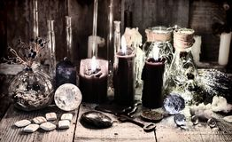 Black candles with runes, crystals, old key, healing herbs and magic ritual objects. Halloween, occult, esoteric and wicca concept. Vintage background with old stock photos