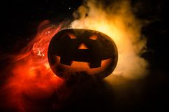 Halloween - old jack-o-lantern on black background. Closeup of scary halloween pumpkins. Halloween - old jack-o-lantern on black foggy background. Closeup of Royalty Free Stock Photo