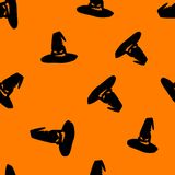 Halloween orange background with angry faces witch hat silhouettes festive seamless pattern. Endless background. Royalty Free Stock Images