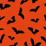 Halloween orange background with bats silhouettes festive seamless pattern. Endless background. Stock Photos