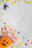 Halloween orange bucket with candies, jujubes, and rubber spider Royalty Free Stock Images