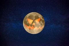 Halloween Orange Full Moon with a terrible mystical face with stars. In the background Stock Photos