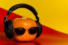 Halloween orange Kürbis im Schwarzen mit Kopfhörern und Sonnenbrille mit einem leeren Raum im Rot mit einem gelben Hintergrund lizenzfreie stockbilder