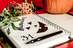 Halloween. orange pumpkin writing pad with painted black Jack. dry foliage dry berries with empty space stock image