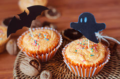 Halloween orange sprinkled cupcakes with pumpkin cream and ghost. Halloween orange sprinkled cupcakes with pumpkin cheese cream and scary ghost and bat royalty free stock photography