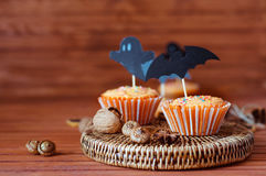 Halloween orange sprinkled cupcakes with pumpkin cream and ghost. Halloween orange sprinkled cupcakes with pumpkin cheese cream and scary ghost and bat royalty free stock image