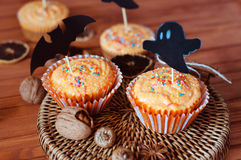 Halloween orange sprinkled cupcakes with pumpkin cream and ghost. Halloween orange sprinkled cupcakes with pumpkin cheese cream and scary ghost and bat stock image