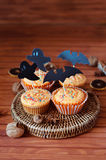 Halloween orange sprinkled cupcakes with pumpkin cream and ghost. Halloween orange sprinkled cupcakes with pumpkin cheese cream and scary ghost and bat royalty free stock images