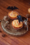 Halloween orange sprinkled cupcakes with pumpkin cream and ghost. Halloween orange sprinkled cupcakes with pumpkin cheese cream and scary ghost and bat royalty free stock photos