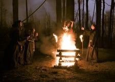 Halloween Os homens na roupa preta, queimam a bruxa na estaca em imagem de stock