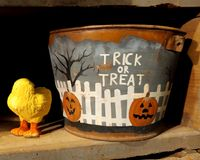 Halloween Pail With Trick or Treat. A tin pail painted with a white picket fence, a black tree and jack-o-lanterns, pumpkins carved that says Trick-or-Treat on stock image