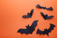Halloween paper bats. On orange background stock photos