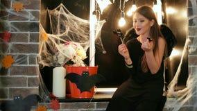 Halloween-Partei, jugendlich Hexenprobierenbonbons, Mädchen, das Spaß an Halloween-Feier, Süßes sonst gibt's Saures hat stock video