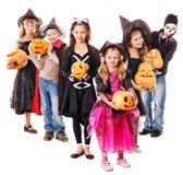 Halloween-Partei mit dem Gruppenkind, welches das Schnitzen des Kürbises hält. Stockbild