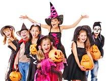 Halloween-Partei mit dem Gruppenkind, welches das Schnitzen des Kürbises hält. Lizenzfreies Stockfoto