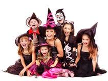 Halloween-Partei mit dem Gruppenkind, welches das Schnitzen des Kürbises hält. Stockfoto
