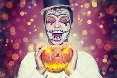 Halloween-partijthema Portret van de mens in masker voor Halloween in zwarte hoed en brandende pompoen ter beschikking royalty-vrije stock fotografie