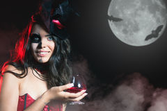 Halloween party 2016! Beautiful woman like witch holding cocktail Royalty Free Stock Images
