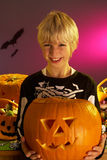 Halloween party with a boy holding pumpkin Stock Image