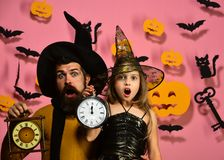 Halloween party and celebration concept. Father and daughter in costumes. Wizard and little witch in black hats hold old clocks. Girl and bearded men with stock photos