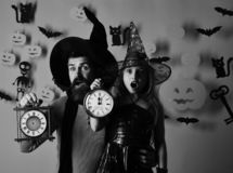 Halloween party and celebration concept. Girl and bearded man. With surprised faces on pink background with decor. Father and daughter in costumes. Wizard and stock images