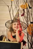 Halloween party and celebration concept. Girl with happy face. On spooky carnival room background. Little witch with Halloween decor. Kid in witch hat and royalty free stock photography
