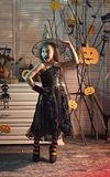 Halloween party and celebration concept. Little witch with Halloween decor. Girl with cheerful face on spooky carnival room background. Kid in witch hat and royalty free stock photos