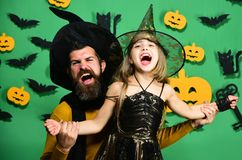 Halloween party and celebration concept. Wizard and little witch. In black hats dance. Girl and bearded men with cheerful faces on green background with decor royalty free stock photos