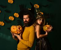 Halloween party and celebration concept. Wizard and little witch. In black hats hold pumpkins. Father and daughter in costumes. Girl and bearded men with stock photography