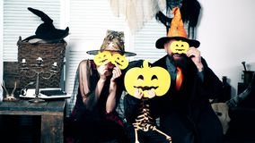 Halloween party and celebration concept. Wizard, witch and the little skeleton hide their faces behind pumpkins. Family stock video footage