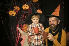 Halloween party and celebration. Boy kid with happy face and bearded men at pumpkin. Halloween men and child in witch hat. Holiday and celebration. Father and royalty free stock image