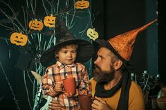 Halloween party and celebration. Father and small son drink from tea or milk cup. Boy kid with happy face and bearded men at pumpkin. Halloween Holiday and stock photo