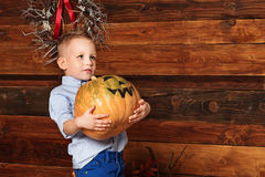 Halloween party with child holding painted heavy pumpkin Royalty Free Stock Images