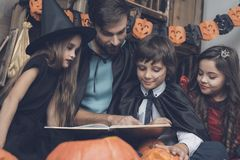 Children in monster costumes sit around a man in a black cloak and read a book at a Halloween party. Halloween party for children. Father reads to children a Stock Photos