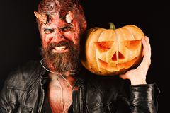 Halloween party concept. Demon with horns and scary face. Holds carved jack o lantern. Devil or monster with October decorations. Man wearing scary makeup holds stock photo
