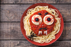Halloween party decoration food. Spaghetti monster. Halloween party creative decoration food. Spaghetti monster face with big eyeballs, fangs, spider and Stock Images