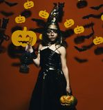Halloween party and decorations concept. Kid in spooky witches costume. Holds carved pumpkin and gas lamp. Girl with serious face on pink background with royalty free stock photography