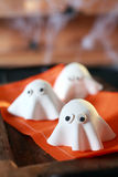 Halloween party decorations from dough. Halloween party decorations from folded pastry dough in the shape of scary little ghosts with big eyes on an orange Stock Photo
