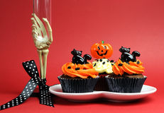 Halloween party food with skeleton hand glass on red background. Stock Photos