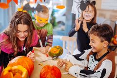 Four children attending Halloween celebration coloring pumpkins together. Halloween party. Four good-looking beaming children attending Halloween celebration royalty free stock photos