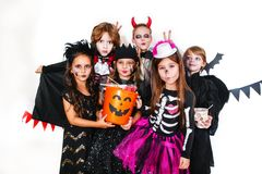 Halloween party. Funny kids in carnival costumes. With pumpkin Stock Image