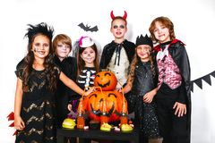 Halloween party. Funny kids in carnival costumes. With pumpkin Stock Images