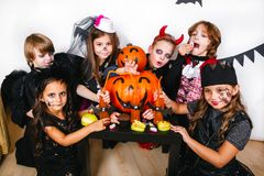 Halloween party. Funny kids in carnival costumes. With pumpkin Stock Photo