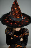 Halloween Party. Girl in image the evil sorcerers. Halloween Party. Girl in image the evil sorcerer. She is dressed in black-orange dress. Wide-brimmed hat Stock Photos