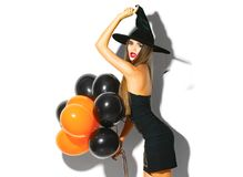 Halloween party girl. Sexy witch holding black and orange air balloons Stock Images