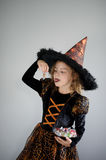 Halloween Party. Girl 8-9 years in image the evil sorcerer. On the girl a black-orange dress and a big hat. Girl holds sweets in hands. She has a ridiculous stock images