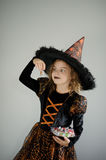 Halloween Party. Girl 8-9 years in image the evil sorcerer. On the girl a black-orange dress and a big hat. Girl holds sweets in hands. She has a ridiculous royalty free stock image