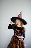 Halloween Party. Girl 8-9 years in image the evil sorcerer. On the girl a black-orange dress and a big hat. Girl holds sweets in hands. She has a ridiculous stock photography