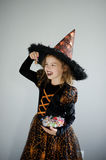 Halloween Party. Girl 8-9 years in image the evil sorcerer. On the girl a black-orange dress and a big hat. Girl holds sweets in hands. She has a ridiculous Stock Image