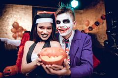 Halloween party. A guy in a Joker costume and a girl in a nun costume posing with a pumpkin-lamp.